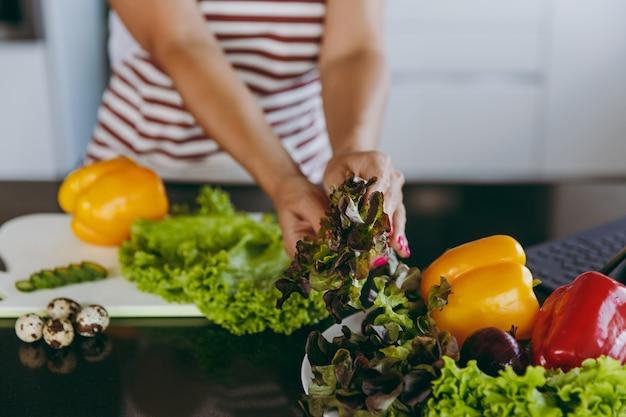 Młoda szczęśliwa kobieta trzyma warzywa w rękach w kuchni z laptopem na stole