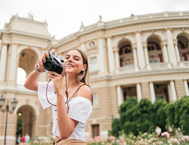 Młoda szczęśliwa kobieta turystycznych trzyma w dłoniach aparat retro przeciwko architekturze turystycznego miasta.