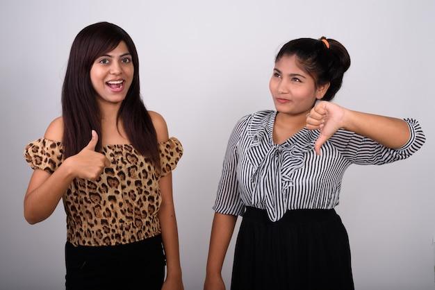 Młoda szczęśliwa kobieta uśmiecha się, dając kciuk do góry z młodą nastolatką myśli, dając kciuk w dół.