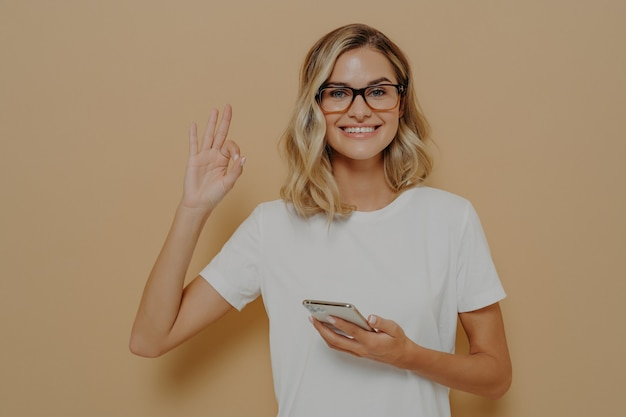 Młoda szczęśliwa kobieta uśmiecha się do kamery i pokazuje dobry gest z nowoczesnym smartfonem w ręku