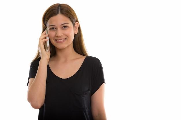 Młoda szczęśliwa kobieta uśmiecha się podczas rozmowy na telefon komórkowy