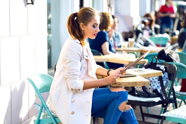 Młoda szczęśliwa kobieta uśmiechnięta i relaksująca na tarasie kawiarni miejskiej, słoneczna pogoda, jasny makijaż, stylowy strój na co dzień, wakacje, podróże, wakacje, radość.