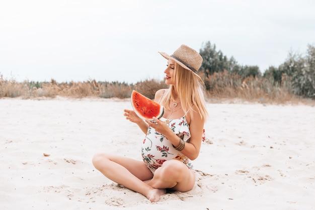 Młoda szczęśliwa kobieta w ciąży w strój kąpielowy i kapelusz z arbuza