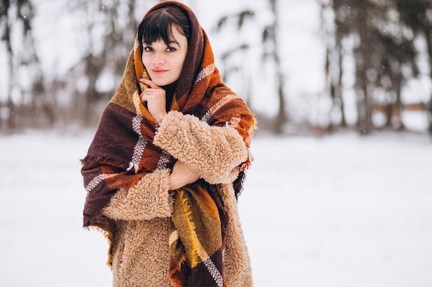 Młoda szczęśliwa kobieta w ciepłych płótnach w zima parku