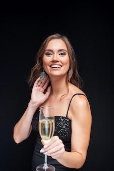 Młoda szczęśliwa kobieta w eleganckiej sukni z lampką szampana na imprezie.