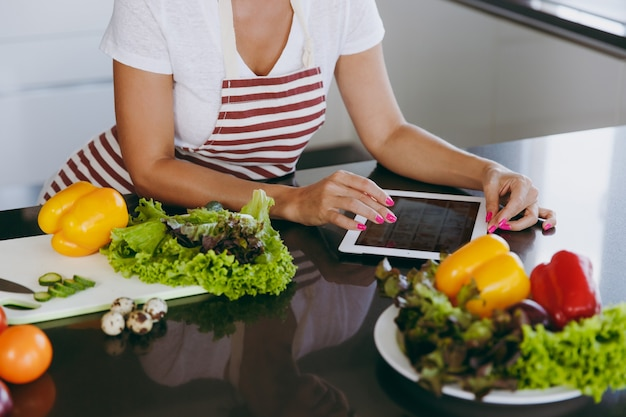 Młoda szczęśliwa kobieta w fartuchu patrząca na przepis na tablecie w kuchni