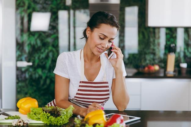 Młoda szczęśliwa kobieta w fartuchu rozmawia przez telefon komórkowy i patrzy na przepis na tablecie w kuchni