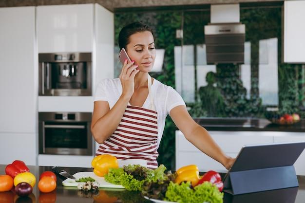 Młoda szczęśliwa kobieta w fartuchu rozmawia przez telefon komórkowy i patrzy na przepis w laptopie w kuchni