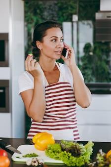 Młoda szczęśliwa kobieta w fartuchu rozmawia przez telefon komórkowy w kuchni