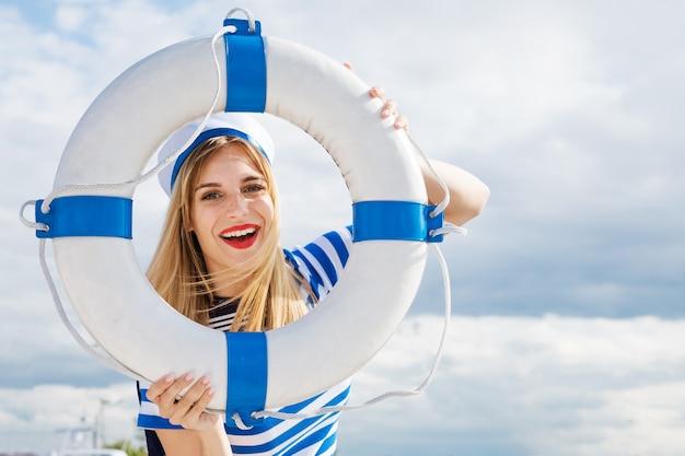 Młoda szczęśliwa kobieta w niebieskiej sukience w paski stojąca na jachcie pozuje z kołem ratunkowym w dłoni