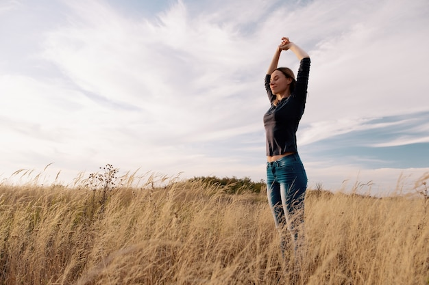 Młoda szczęśliwa kobieta w złotym polu na zmierzchu.