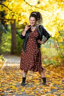 Młoda szczęśliwa kobieta z dredami na zewnątrz jesienią, koncepcja kultury młodzieżowej
