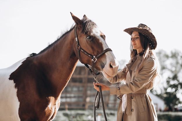 Młoda szczęśliwa kobieta z koniem przy rancho