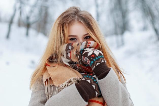 Młoda szczęśliwa kobieta z pięknymi brązowymi oczami w zimowe modne ciepłe ubrania w zabytkowych rękawiczkach w zimowym lesie. zabawna stylowa dziewczyna z szalikiem na twarzy.