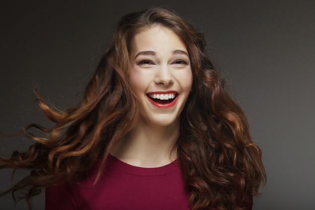 Młoda szczęśliwa kobieta z wiatrem w włosy