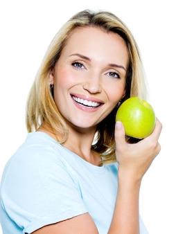 Młoda szczęśliwa kobieta z zielonym jabłkiem - na białej przestrzeni