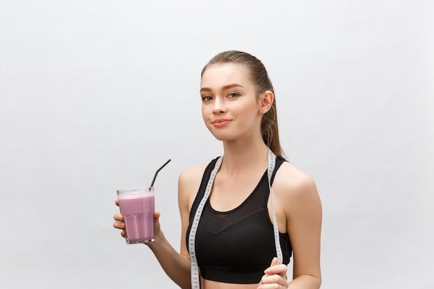 Młoda szczęśliwa kobieta ze zdrowej diety wstrząsnąć picia dla sportu i fitness.
