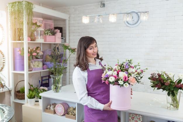 Młoda szczęśliwa kwiaciarnia robi świeżemu kwiatowi układowi w prezenta pudełku