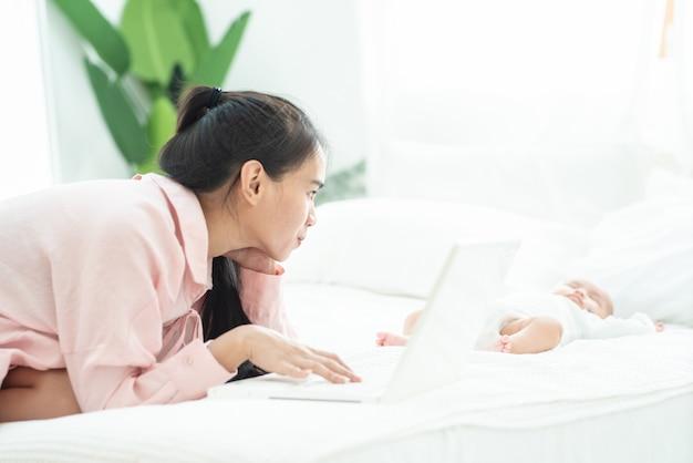 Młoda szczęśliwa macierzysta azjatykcia kobiety praca na laptopie na łóżku bierze opieka nowonarodzonego sen, pracuje w domu i pepiniery opieki pojęcie.