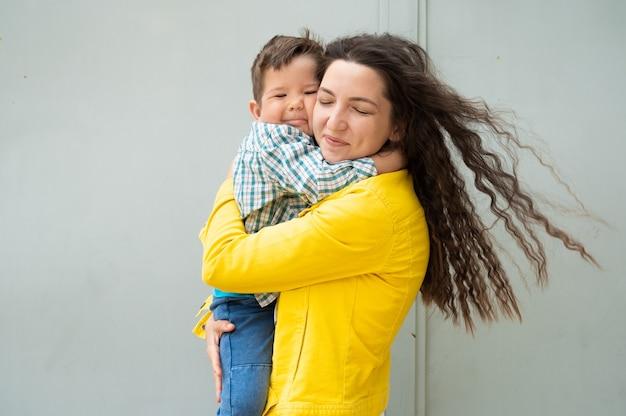 Młoda szczęśliwa mama trzyma dziecko w ramionach.