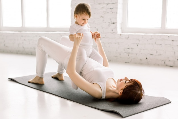 Młoda szczęśliwa matka ćwiczy, robi ćwiczenia mostkowe, nosi białą odzież sportową, małą córeczkę na brzuchu, fitness, jogę poporodową
