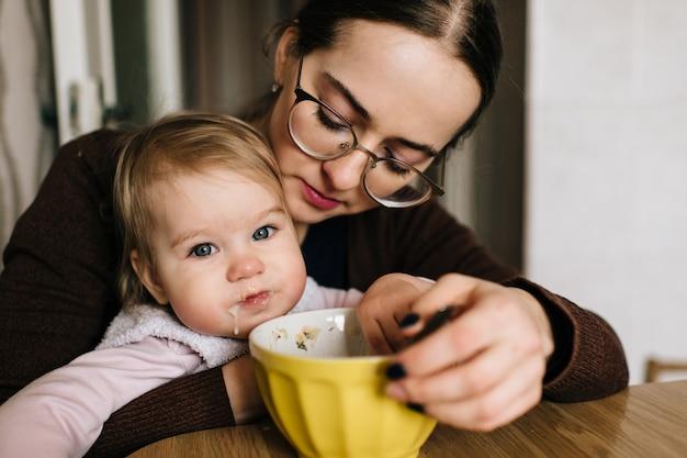 Młoda szczęśliwa matka karmi jej małego dziecka przy stołem.