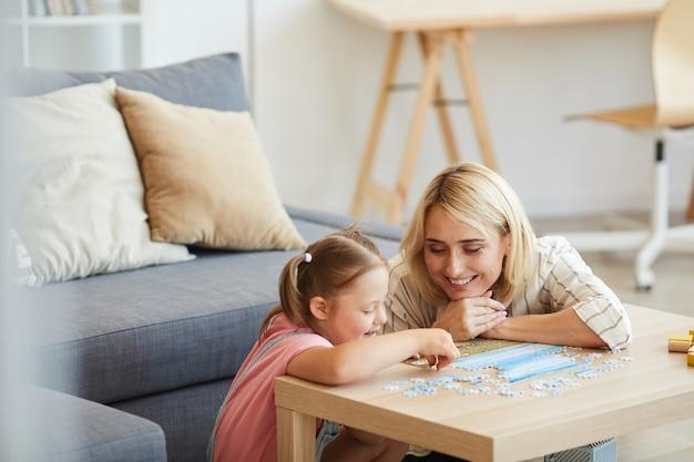 Młoda szczęśliwa matka uczy swoją córkę z zespołem downa, zbierając puzzle przy stole w salonie