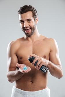 Młoda szczęśliwa mężczyzna pozycja odizolowywająca mienia golenia pianka