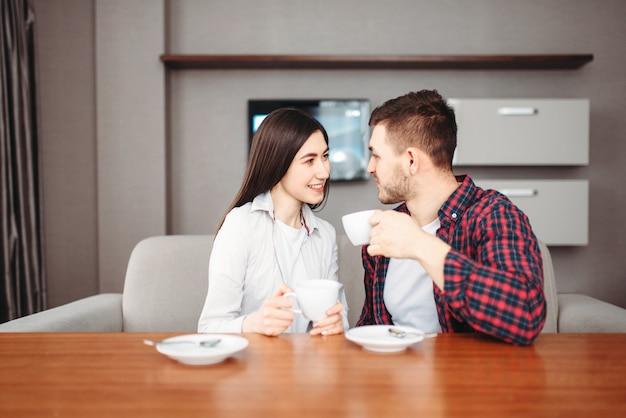 Młoda szczęśliwa miłość para pije kawę przy drewnianym stole w godzinach porannych.