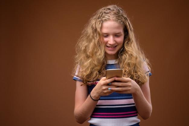 Młoda szczęśliwa nastolatka sms-y z telefonu komórkowego podczas uśmiechu