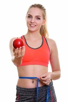 Młoda szczęśliwa nastolatka uśmiecha się dając czerwone jabłko