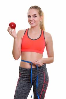 Młoda szczęśliwa nastolatka uśmiecha się trzymając czerwone jabłko
