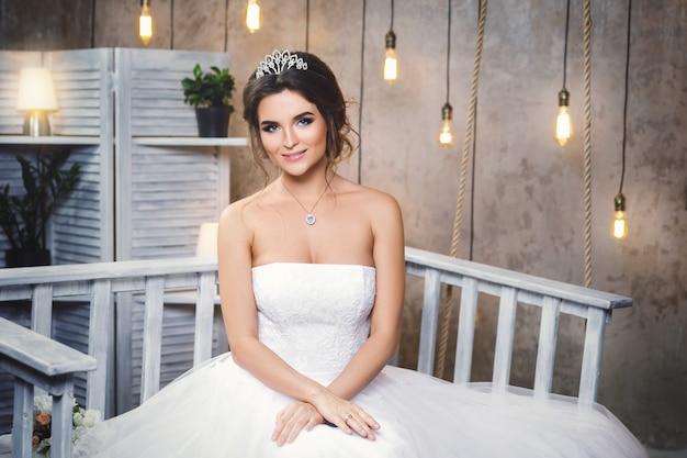 Młoda szczęśliwa panna młoda ubrana w piękną bujną sukienkę w pokoju z dużą ilością żarówek
