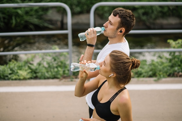 Młoda szczęśliwa para biegająca w parku miejskim z plastikową butelką wody w rękach, wspólne sporty, radość, zdrowy styl życia w mieście, fitness razem, biegacze, woda pitna, pragnienie