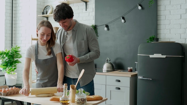 Młoda szczęśliwa para cieszy się i przygotowuje zdrowy posiłek w swojej kuchni