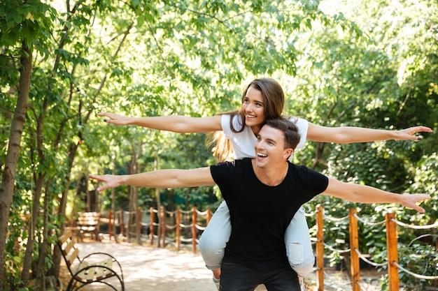 Młoda szczęśliwa para cieszy się piggyback przejażdżkę przy parkiem