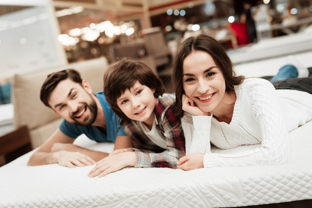 Młoda szczęśliwa para i mała dziewczynka na łóżku w sklepie