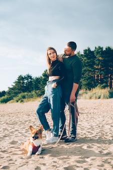 Młoda szczęśliwa para i pies stojący na plaży przed sosnami i piaskiem