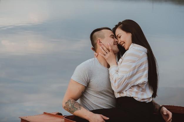 Młoda szczęśliwa para kaukaska przytulanie i uśmiech na plaży nad rzeką