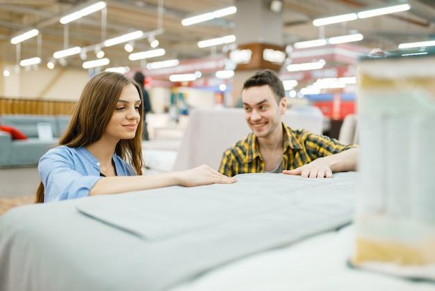 Młoda szczęśliwa para kupuje koc do łóżka w sklepie meblowym.
