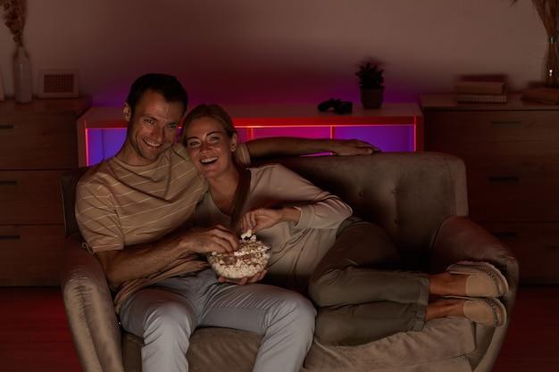 Młoda szczęśliwa para leżąc na kanapie z popcornem i oglądając film w czasie wolnym w domu