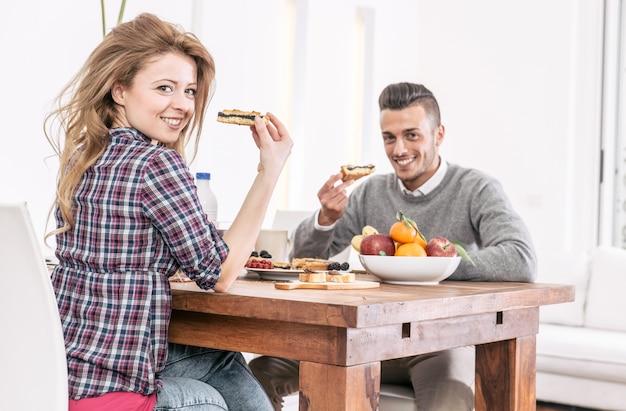 Młoda szczęśliwa para ma śniadanie w ranku