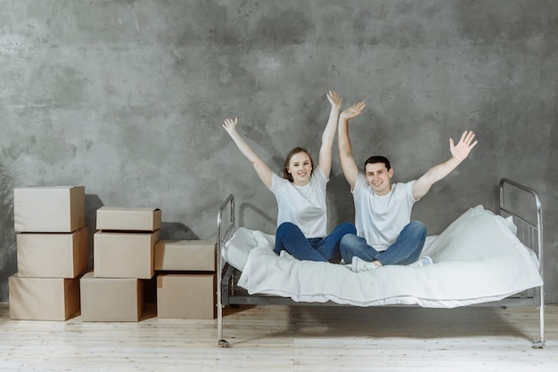 Młoda szczęśliwa para mężczyzna i kobieta przenoszą się do pustego domu, siedząc na łóżku wraz z podniesionymi rękami