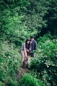 Młoda szczęśliwa para mężczyzna i kobieta z psem siedzimy przy gazonie