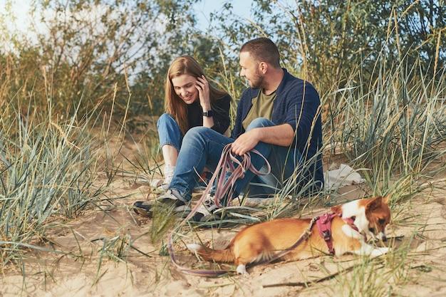 Młoda szczęśliwa para mężczyzny i kobiety z psem corgi siedzieć na piasku