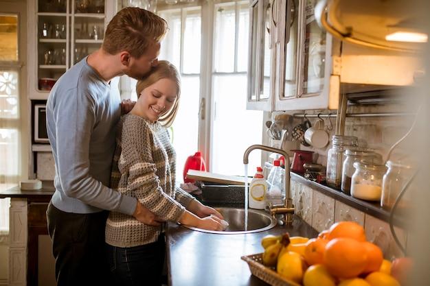 Młoda szczęśliwa para myje naczynia