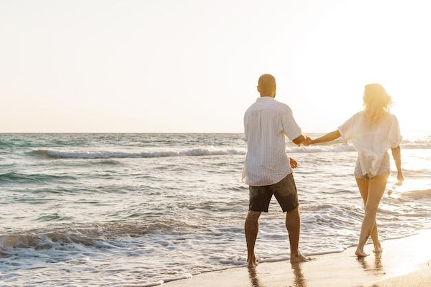 Młoda szczęśliwa para na brzegu morza, ciesząc się morzem