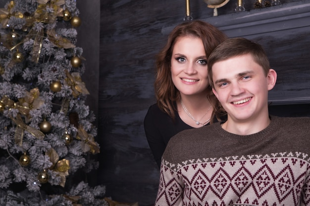 Młoda szczęśliwa para obejmuje blisko choinki świętuje nowego roku wpólnie ono uśmiecha się