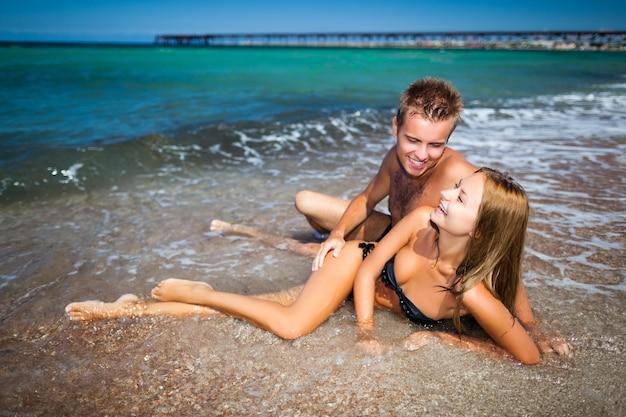 Młoda szczęśliwa para piękny kobieta i mężczyzna leżący w wodzie morskiej z plaży