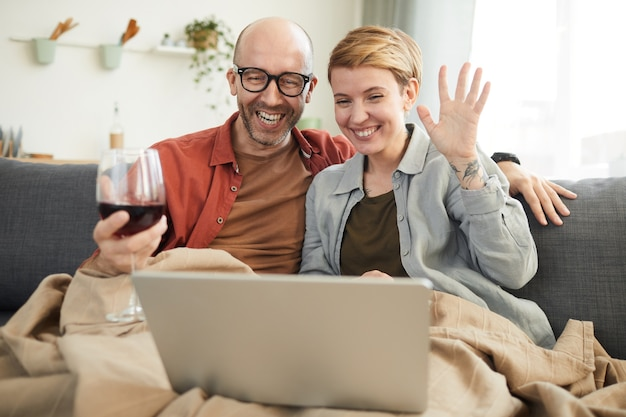 Młoda szczęśliwa para pije czerwone wino i komunikuje się online z przyjaciółmi w domu